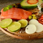 Fresh vegetables and smoked fish on wooden board in rustic kitchen. Salmon, lime, onions, olives, tomatoes and olive oil. Focus on foreground.